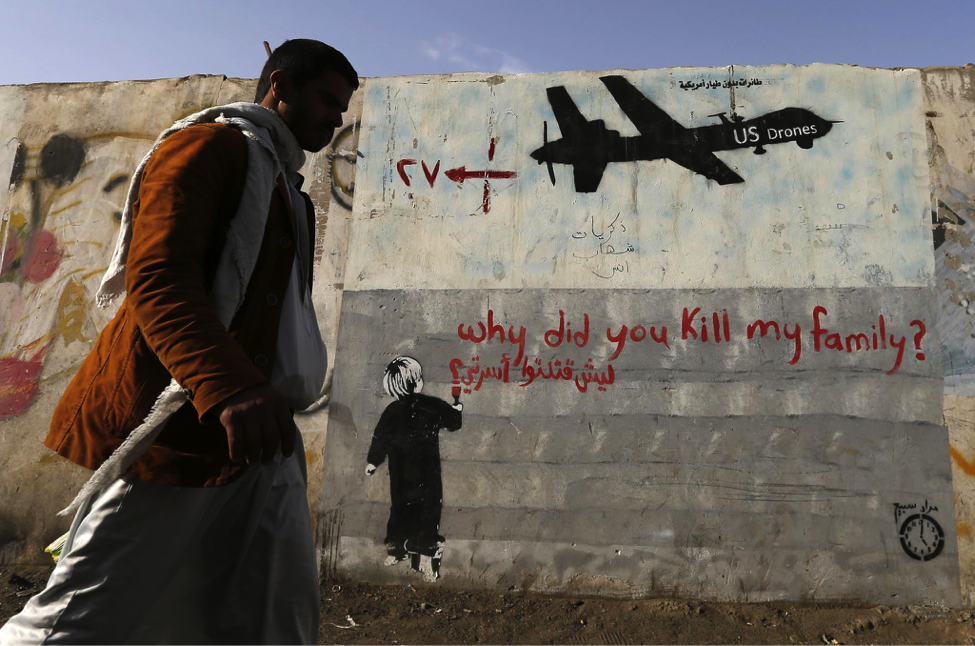 A man walks past a graffiti, denouncing strikes by U.S. drones in Yemen, painted on a wall in Sanaa November 13, 2014